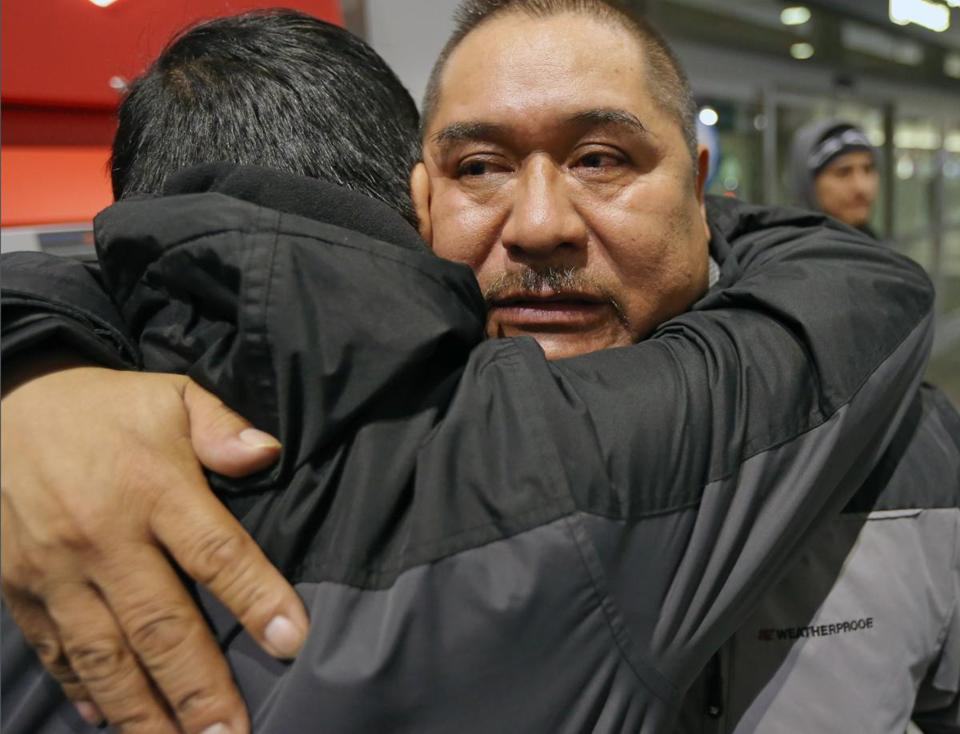 At Logan airport, Terminal A for a 5:45 am flight, Isidro Macario gives his son Isidro Jr, a hug goodbye.